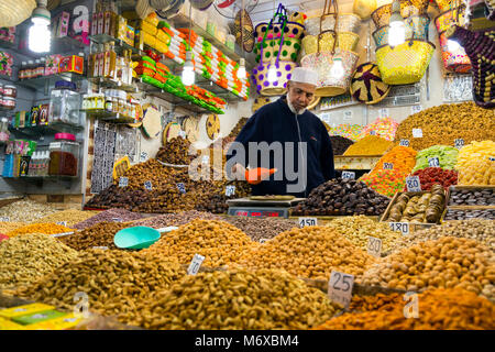 A vendor selling and weighing nuts out of his stall in the Old Medina souqs in Marrakesh, Morocco - Stock Photo