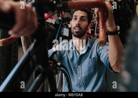Man inspecting a bicycle handle for alignment. Mechanic working on fixing a bicycle in workshop. - Stock Photo