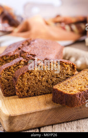 Healthy vegan freshly baked homemade pumpkin cake with ingredients on rustic wooden board, sliced and ready to eat - Stock Photo