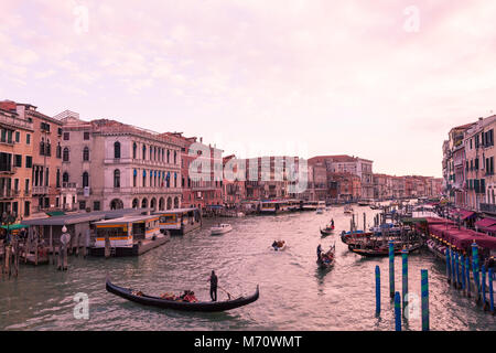 Colorful pink sunset  at dusk over the Grand Canal, Venice, Italy as viewed from Rialto Bridge over Riva del Vin - Stock Photo