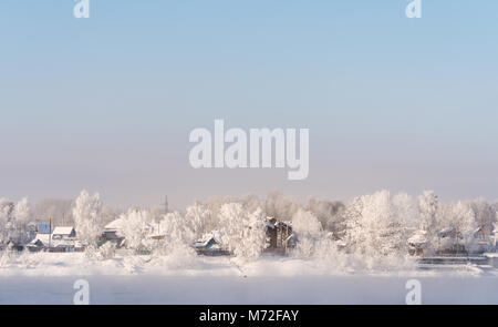 Winter landscape, white snow covered on trees and local houses in urban countryside, in Russia - Stock Photo
