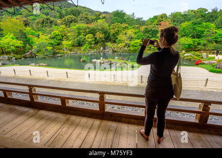 Kyoto, Japan - April 27, 2017: japanese woman from Hojo Hall photographs Sogen Garden around Sogen-chi Pond in Tenryu - Stock Photo