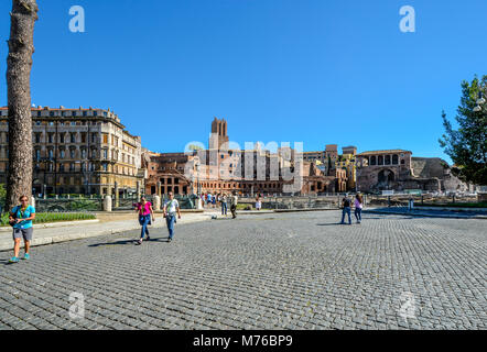 Ancient ruins of Trajan's Market near the Colosseum and Roman Forum on a sunny day as tourists enjoy walking in - Stock Photo