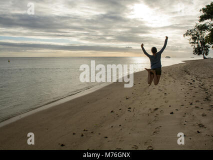 A young woman jumps into the air to celebrate being in a tropical paradise. Foot steps all around her from others - Stock Photo