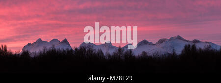 Panorama view of the mountain range Børvasstindene Shot during sunrise in winter season. - Stock Photo