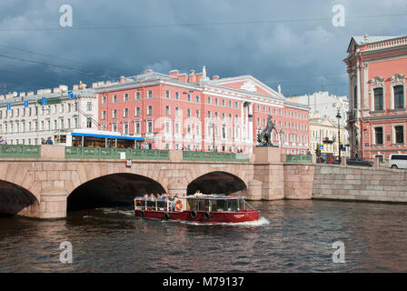 People in the tourist boat sail on the Fontanka River under The Anichkov Bridge with The Horse Tamers by Peter Klodt - Stock Photo