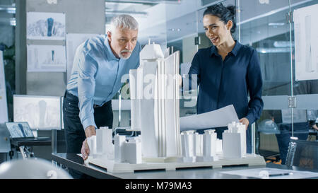 In the Architectural Bureau Two Professional Engineers Work on a Model of a City District. Urban Planners Work on - Stock Photo