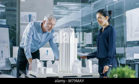 In the Architectural Bureau Female Engineer Brings Blueprints and Shows them to  Senior Architect, They Discuss - Stock Photo