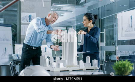 Two Professional Male and Female Architectural Engineers Work with Blueprints and on a Building Model Design for - Stock Photo