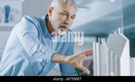 Male Senior Engineer and Female Architectural Designer Work on a Building Model Design for the Urban Planning Project. - Stock Photo