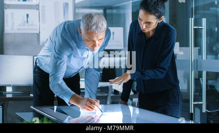 Senior Male and Young Female Architectural Designers Draw Building Concept on a Graphics Tablet Display Vertical - Stock Photo