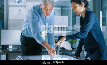 Senior Male and Young Female Architectural Designers Draw Building Concept on a GraphicsTablet Display Vertical - Stock Photo