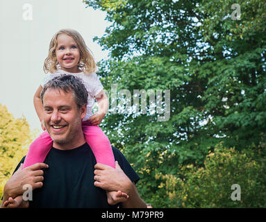 A 2 year old girl being piggy backed by her father. - Stock Photo