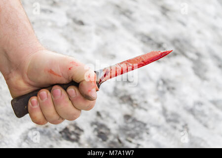 dirty man's hand with a bloody knife on the ground with snow background - Stock Photo