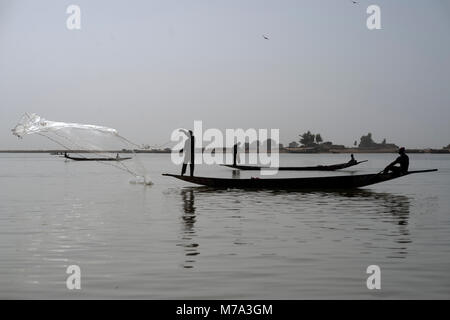 A fisherman casts his net while standing in his boat on the River Niger. Mopti, Mali, West Africa. - Stock Photo