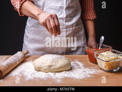 Woman sprinkles flour onto pizza dough on the cutting board. - Stock Photo
