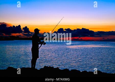 Silhouette of a man fishing in the sea, Varadero, Matanzas, Cuba - Stock Photo