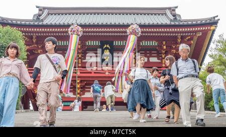 Japanese tourists walking down stone stairs in front of Tsurugaoka Hachimangū shinto shrine decorated with large - Stock Photo