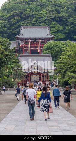 Japanese couple walking up stone path to the entrance of Tsurugaoka Hachimangū shrine in Kamakura Japan with large - Stock Photo