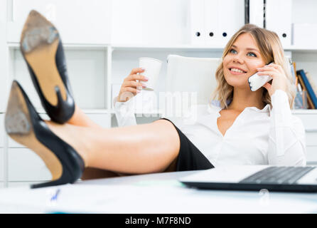 Laid-back girl in corporate-type clothes puts her feet on table and speaks by phone in office - Stock Photo