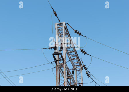 Train or railway power line support. Railway power lines with high voltage electricity on metal poles against blue - Stock Photo