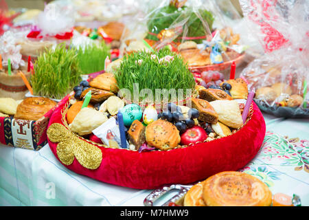 Plate with national sweets pastry for Novruz celebration in Azerbaijan, shekerbura and pakhlava with fresh green - Stock Photo