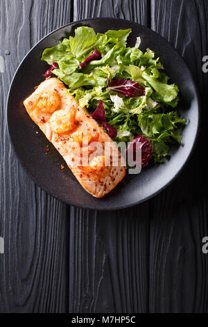 Baked salmon with prawns and honey sauce with a side dish of salad mix close-up on a plate on a table. Vertical - Stock Photo