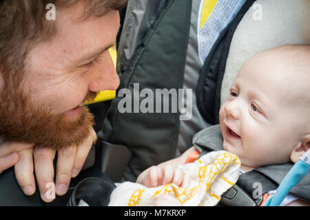 A man smiling at this infant son. 3 months old. - Stock Photo