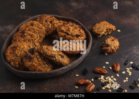 Homemade vegan oatmeal cookies with raisins, pecans and dates. Healthy vegetarian dessert concept. Dark rusty background, - Stock Photo