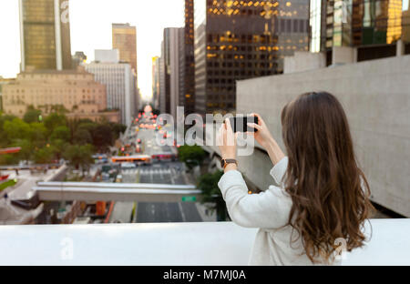Beautiful young woman sitting on a bridge across the boulevard in urban scenery, downtown, at sunset, taking photos - Stock Photo