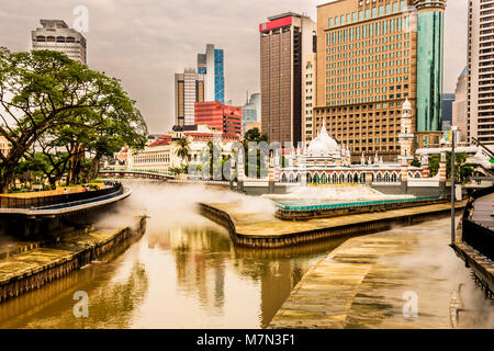View of the Klang River Fountains and Financial Center in Kuala Lumpur Malaysia - Stock Photo