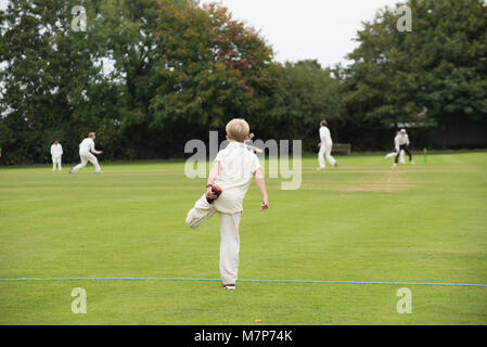 close up of young cricket player warming up before joining the field in a village school youth team - Stock Photo