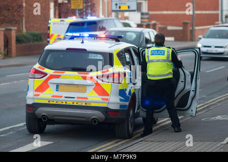 policeman enters vehicle with blue lights flashing and police riot van in background - Stock Photo