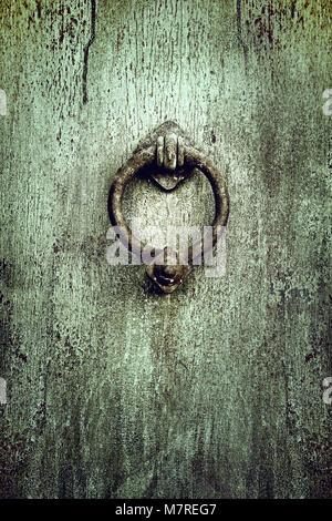 Old rusty knob or knocker on aged metallic retro door - Stock Photo