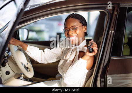 Beautiful young mixed race black African American woman driving car and show holding the key - Stock Photo