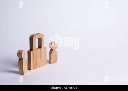 Two people stand near a padlock and keep secrets, information, entrance. Wooden figures of persons carry guards - Stock Photo