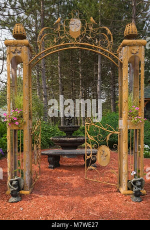 Golden wrought iron metal arbour gate decorated with pink Petunia flowers and cascading water fountain in private - Stock Photo