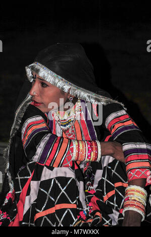 Bejeweled woman dressed in colourful clothing with black fringed dupatta covering head. Portrait of a dancer against - Stock Photo