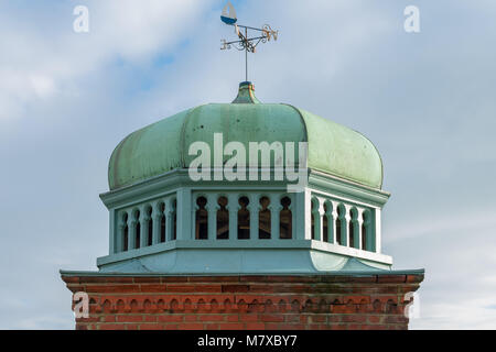 Copper green dome in Bexhill-on-Sea on a brick base, with a weathervane on top, photographed in the early spring - Stock Photo