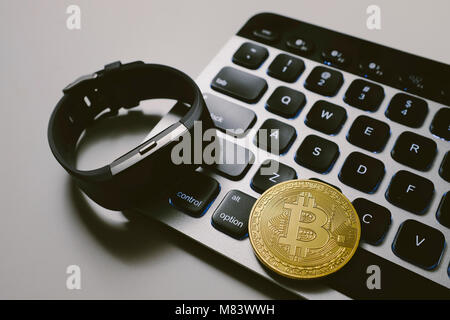Bitcoin on keyboard with fitness tracker watch - Stock Photo