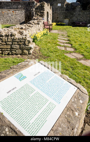 Bilingual, English and Welsh, tourist information sign in front of the sunlit ruins of Barry castle. - Stock Photo