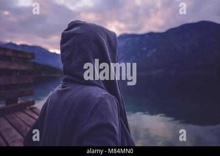 Lonely hooded female person standing by the lake and looking at beautiful mountain and forest landscape in sunset, - Stock Photo