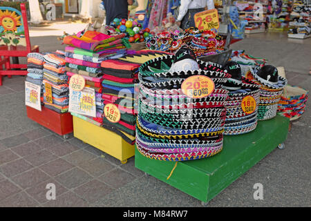 Tourist souvenirs on display on the malecon in Puerto Vallarta, Mexico include items associated with perceived Mexican - Stock Photo