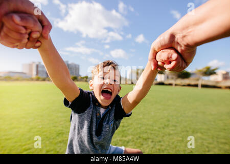 Cheerful boy enjoys being lifted in air while playing in a park. Close up of a boy in playful mood at a park. - Stock Photo