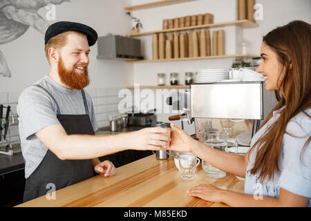 Coffee Business Concept - young beared handsome barista talking and giving take away hot coffee for beautiful caucasian - Stock Photo