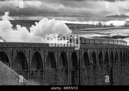 Puffing steam cloud, iconic locomotive LNER class A3 60103 Flying Scotsman, travels over arches of Ribblehead Viaduct - Stock Photo