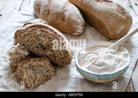 Whole grain bread  and flour on light background. Ceramic bowl full of whole grain flour - Stock Photo