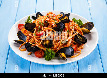 Cooked mussels and pasta on wooden table - Stock Photo