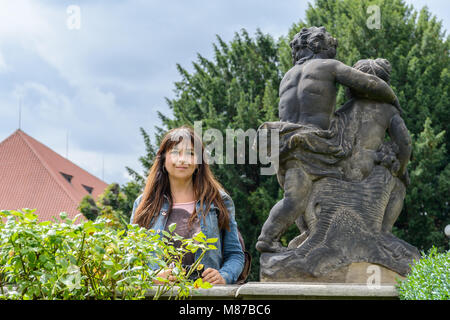 A tourist girl posing inside The wonderful gardens outside the Prague Castle - Stock Photo