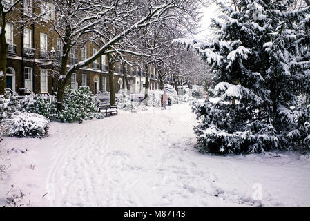 Public park bench victorian houses behind covered with snow London winter - Stock Photo